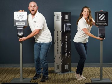 Alex Carroll (left) and Kelsey Carroll ham it up at their offices on Monday, May 18, 2020, in Irving. Due to the COVID-19 pandemic, the husband and wife team transitioned their party planning business, Toss Up Events, to providing hand sanitizer machines as a new business called Stand Up Stations.  (Smiley N. Pool/The Dallas Morning News)