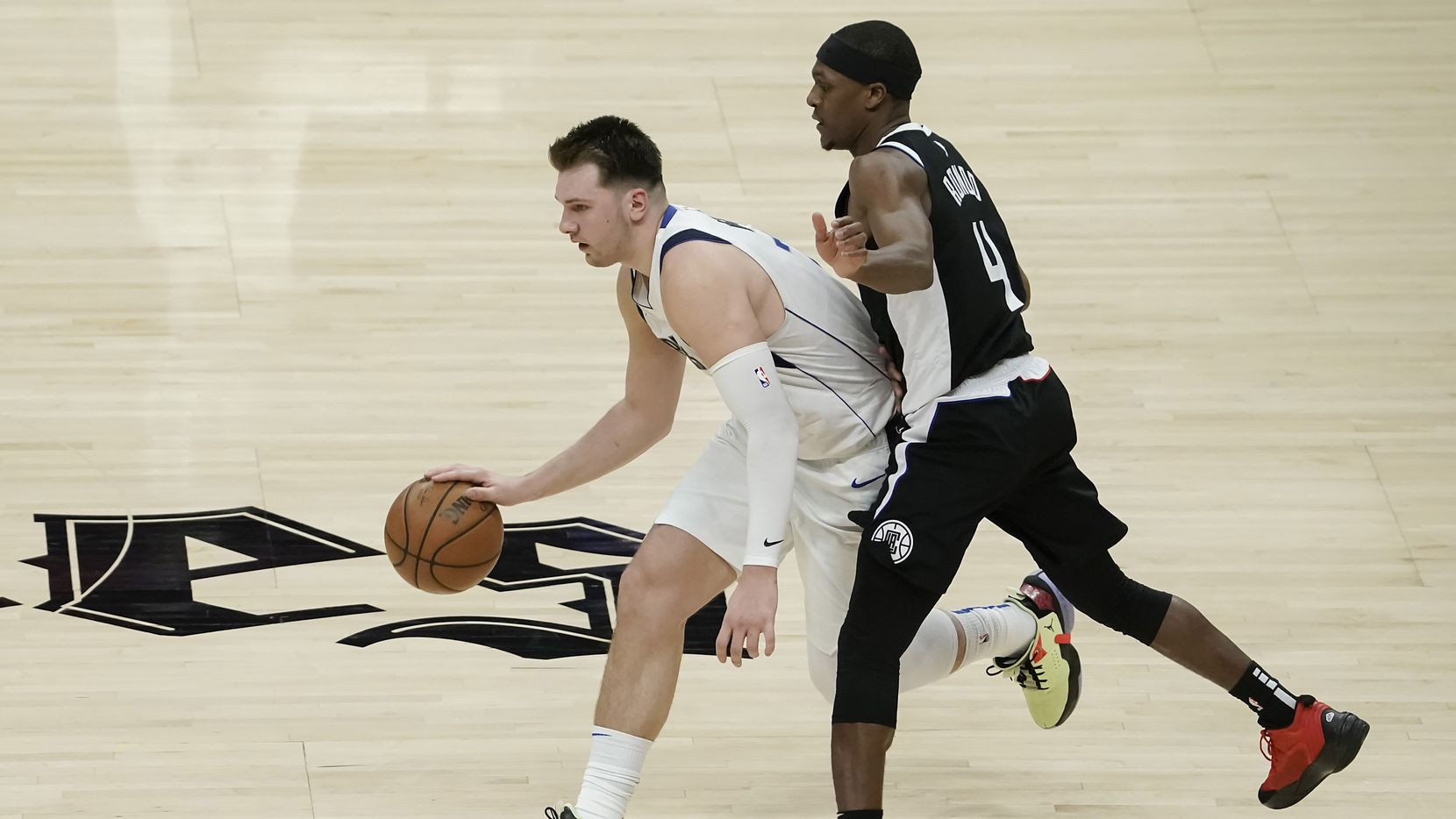 Dallas Mavericks guard Luka Doncic (77) gets past LA Clippers guard Rajon Rondo (4) during the second half of an NBA playoff basketball game at Staples Center on Saturday, May 22, 2021, in Los Angeles. The Mavericks won the game 113-103.
