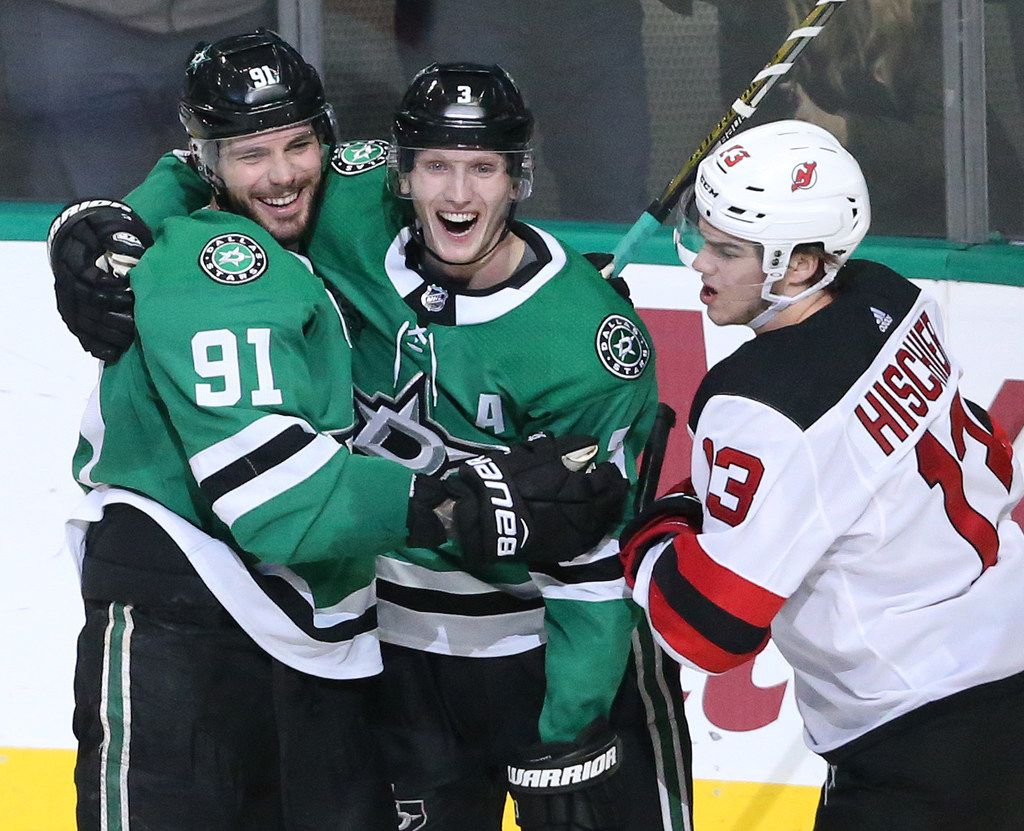 Dallas Stars Tyler Seguin (91) and John Klingberg (3) celebrate Seguin's goal in the second period as New Jersey Devils Nico Hischier (13) skates past during the New Jersey Devils vs. the Dallas Stars NHL hockey game at the American Airlines Center in Dallas on Thursday, January 4, 2018. (Louis DeLuca/The Dallas Morning News)