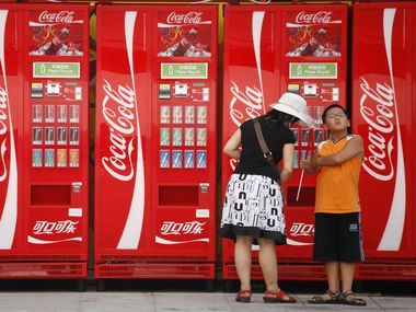 In this file photo, a woman and boy stand near Coca-Cola vending machines on the Olympic Green at the 2008 Beijing Olympics in Beijing.