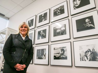 Paige Flink poses next to a wall of photographs of former Family Place clients photographed by Judy Walgren more than 20 years ago. Flink is retiring as the CEO of the family center after 30 years of service.