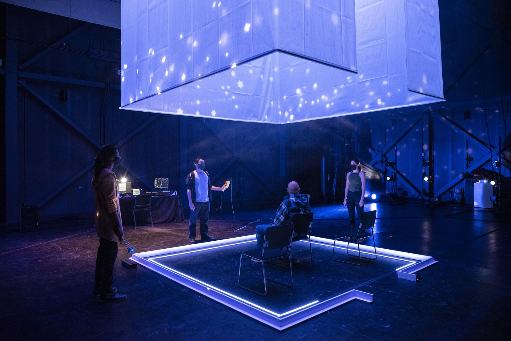 """Near the end of """"The Cube"""" at the Latino Cultural Center, the curtains rise and the cast surrounds the tiny audience of one to three people for a moment of masked, socially distanced human connection."""