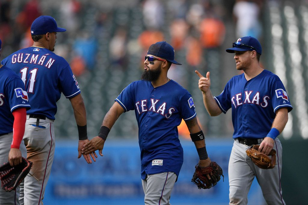 Texas Rangers' Ronald Guzman (11), Rougned Odor, center, and Logan Forsythe, right, celebrate after a baseball game against the Baltimore Orioles, Sunday, Sept. 8, 2019, in Baltimore. The Rangers won 10-4.(AP Photo/Nick Wass)