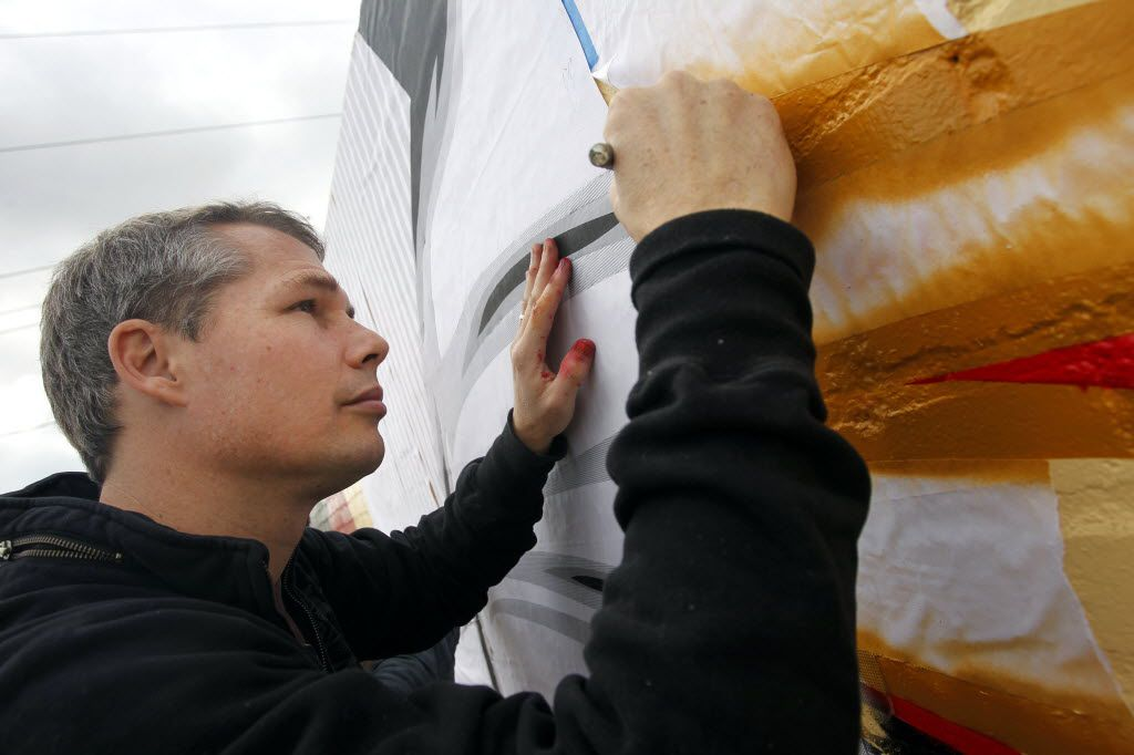 """Graphic artist Shepard Fairey worked on painting a mural titled """"Harmony"""" on the building at 331 Singleton Blvd. in Dallas on Jan. 31, 2012."""