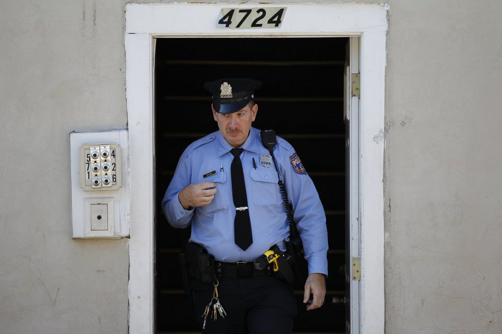 A policeman exits the front doorway of an apartment building.