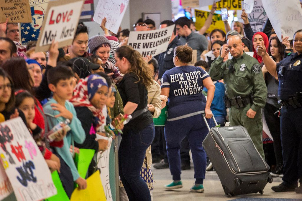Police keep a walkway clear for arriving passengers in the international arrivals hall at DFW International Airport as protesters fill the hall in opposition to President Donald Trump's executive order barring certain travelers on Sunday, Jan. 29, 2017. Multiple travelers were detained at DFW after Trump shuts borders. (Smiley N. Pool/The Dallas Morning News)