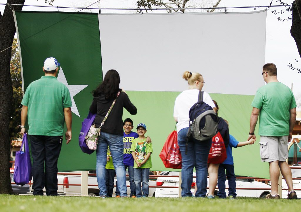Visitors pose for photos in front of a St. Patrick's day themed Texas flag during the Fort Worth Stock Yard's Cowtown Goes Green event, Saturday, March 14, 2015. (Brandon Wade/Special Contributor)