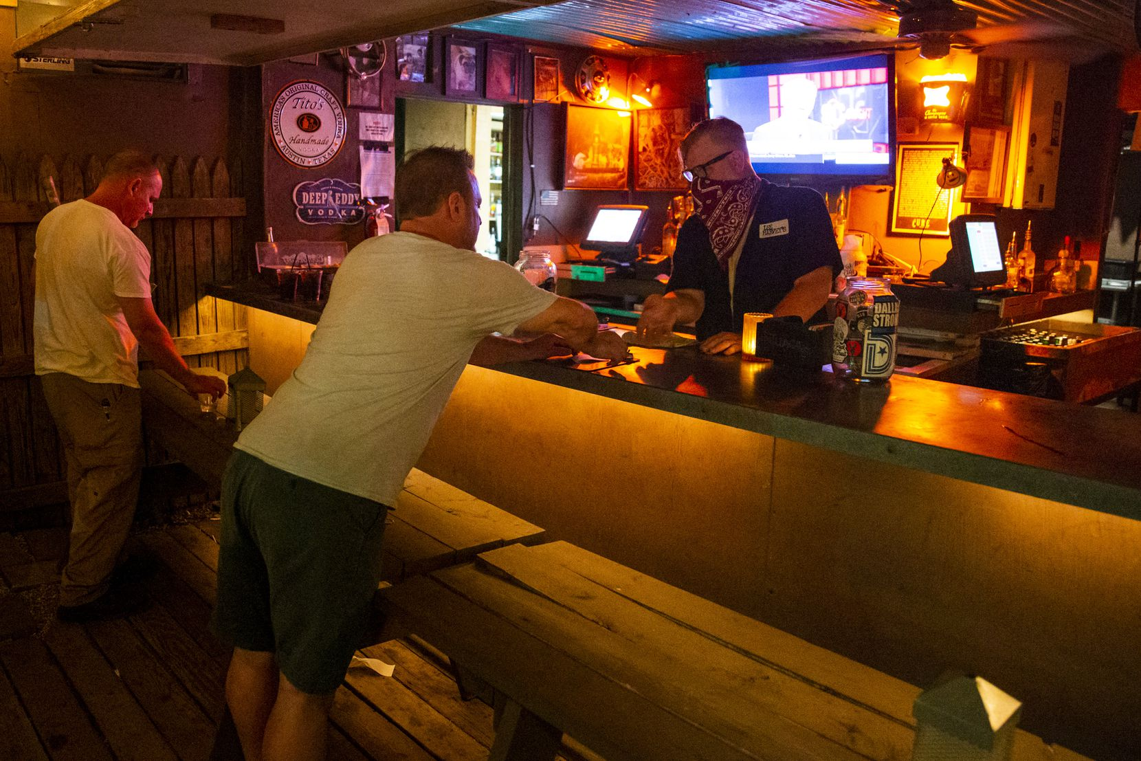 Customers settle up on their tabs with employee Zachary Anderson at the Lee Harvey's bar.