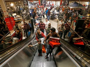 Shopper Puneet Dua (right), his wife Richa (left) and 3-year-old son Mansh ride an escalator while shopping at the J. C. Penney store inside Collin Creek Mall in Plano. Plano is among the best places in the country for those seeking jobs, according to a new study.