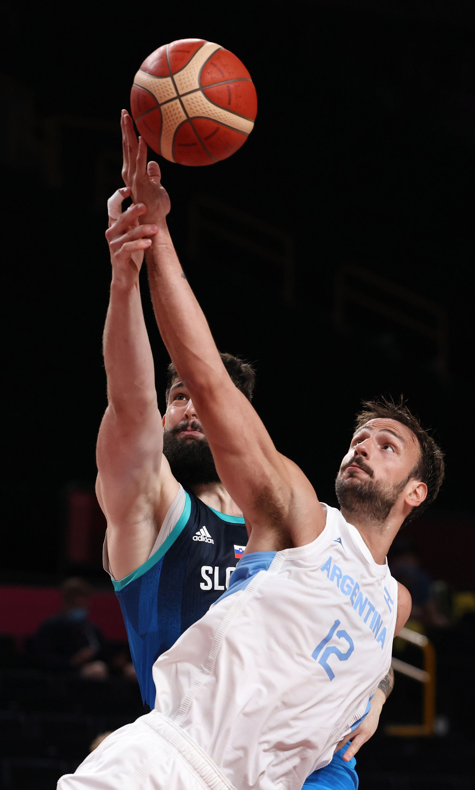 Slovenia's Ziga Dimec (27) and Argentina's Marcos Delia (12) go after the rebound in the first half of play during the postponed 2020 Tokyo Olympics at Saitama Super Arena on Monday, July 26, 2021, in Saitama, Japan. Slovenia defeated Argentina 118-100. (Vernon Bryant/The Dallas Morning News)