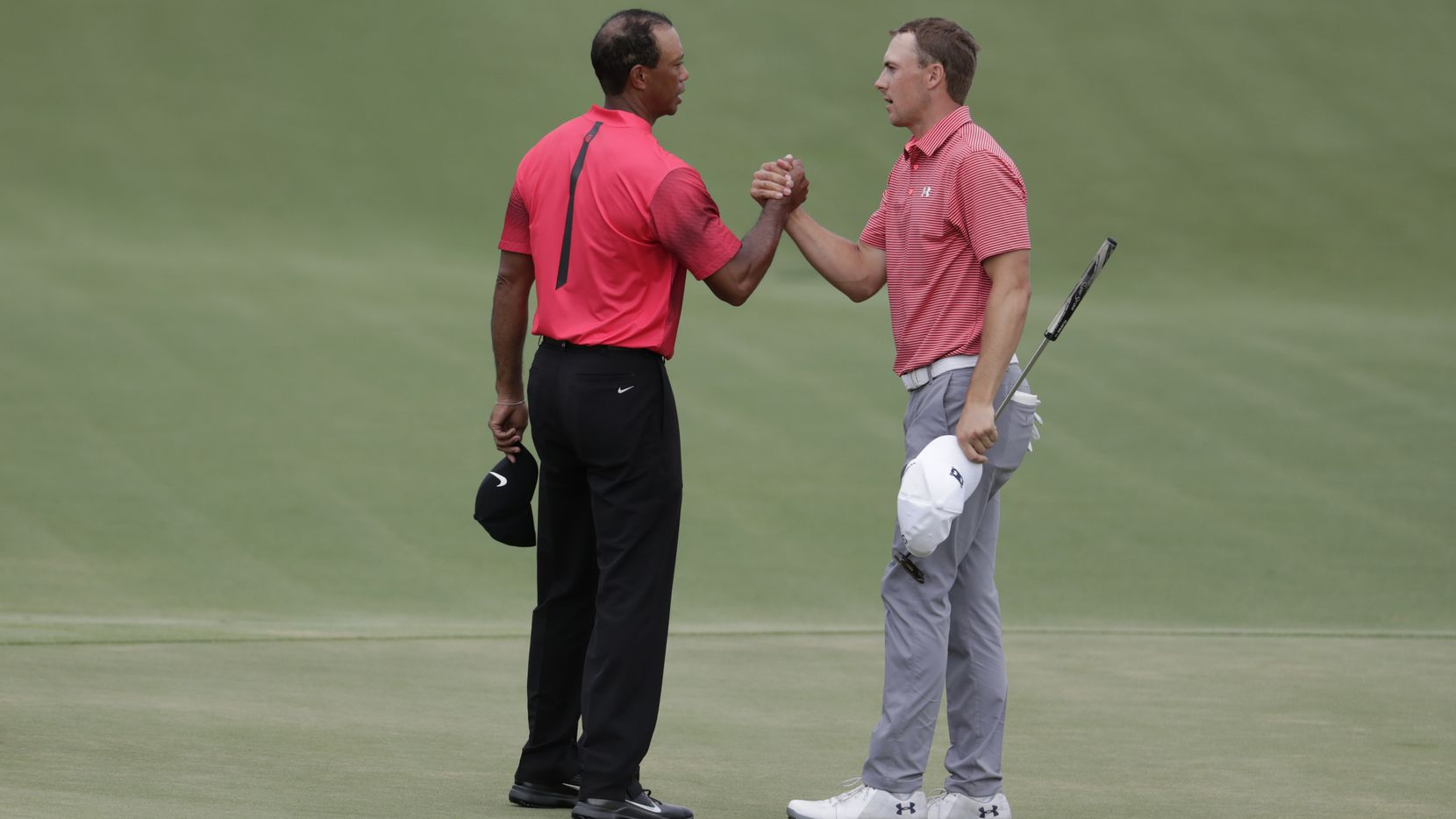 Tiger Woods, left, shakes hands with Jordan Spieth after the final round of the Players Championship golf tournament, Sunday, May 13, 2018, in Ponte Vedra Beach, Fla. (AP Photo/Lynne Sladky)