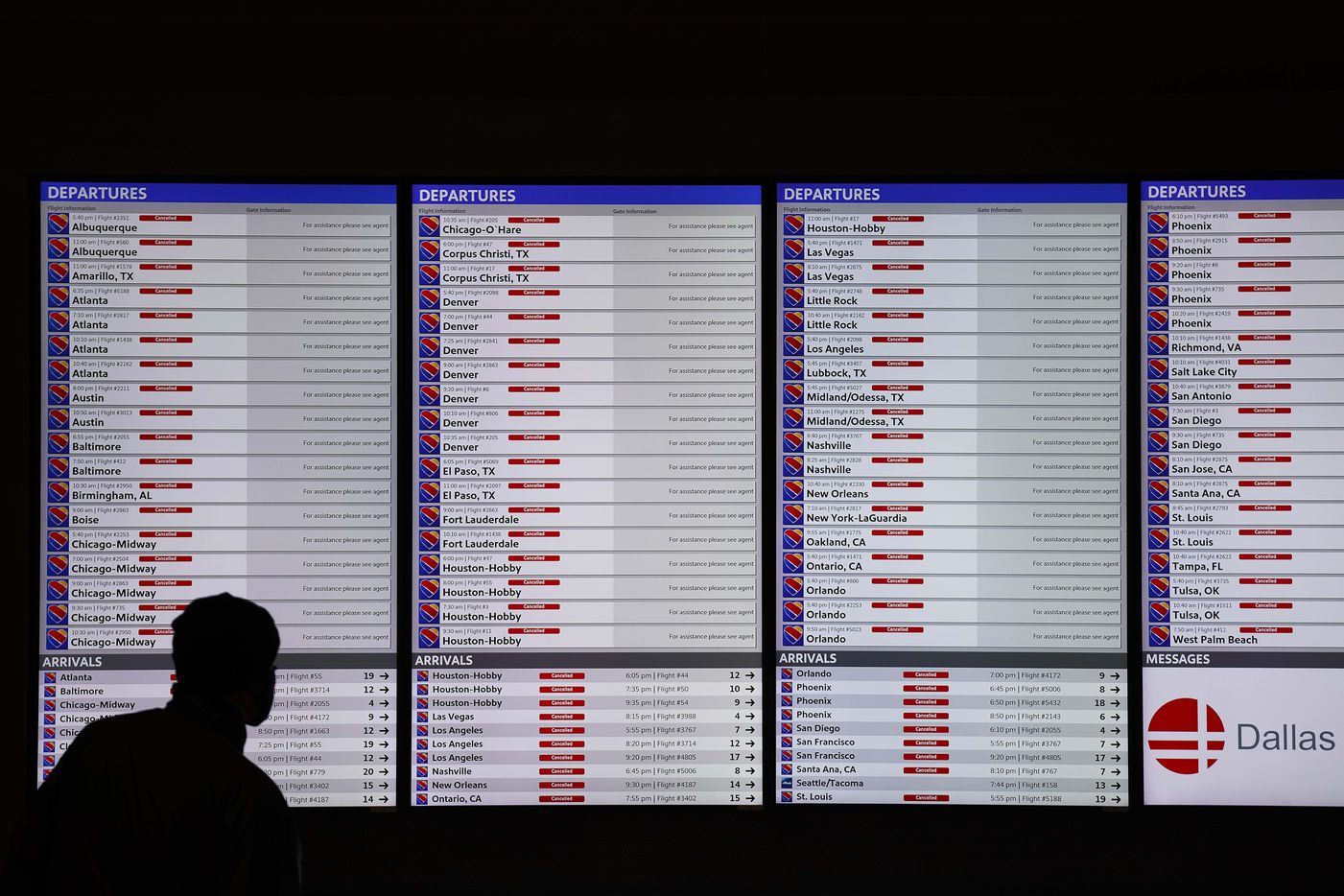 Flight status boards show all flights cancelled at Dallas Love Field as a winter storm brings snow and freezing temperatures to North Texas on Sunday, Feb. 14, 2021, in Dallas.  By evening all commercial flights were cancelled and all ticket counters were closed at the airport.
