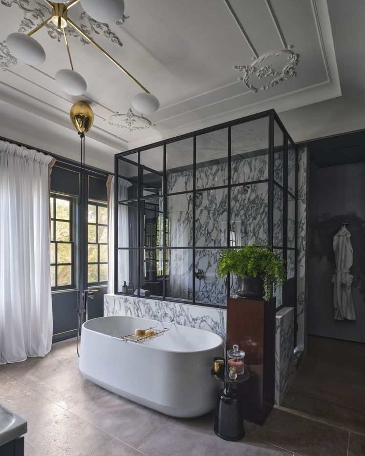 The primary bathroom at the 2021 Kips Bay Decorator Show House Dallas was designed by Brant McFarlain Design. The room features vintage lighting and intricate plaster designs on the ceiling coupled with a modern layout and a balance of masculine and feminine elements.