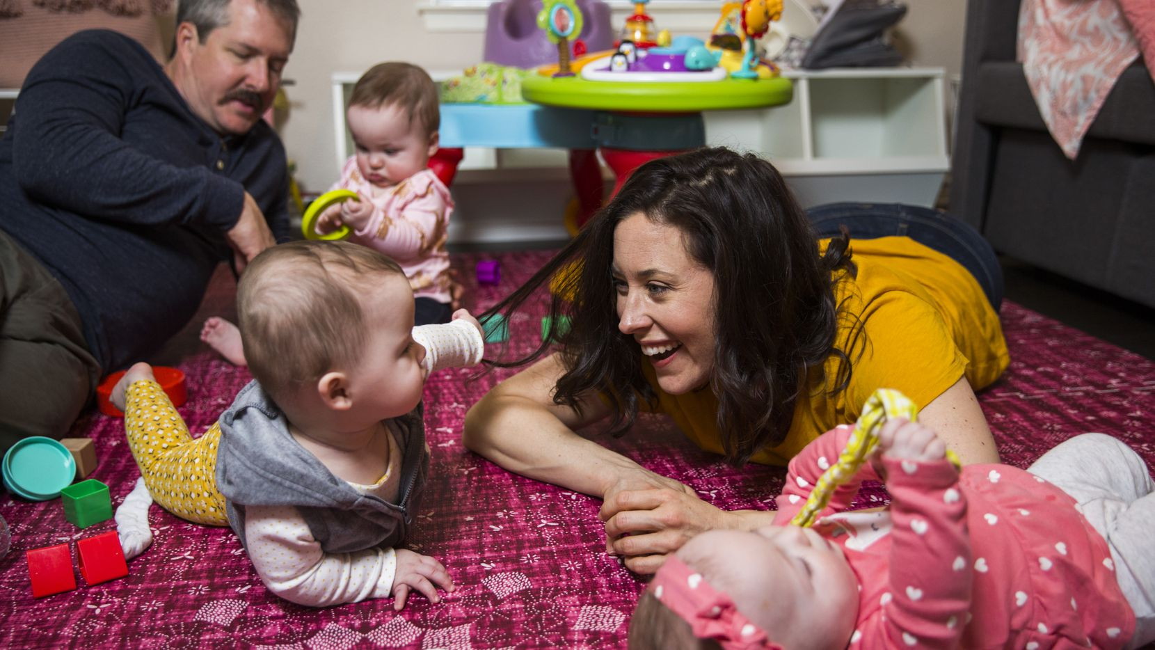 Actress Allison Pistorius (right) and her husband, actor Chris Hury, play with their triplets, Austen Finch Pistorius Hury (top, with her dad), Birdie Sue Pistorius Hury (right) and Charlie Faye Pistorius Hury (center, with her mom), on Wednesday, October 9, 2019. Pistorius, who had triplets 11 months ago, is playing the part of Dracula at Theatre Three in Dallas.