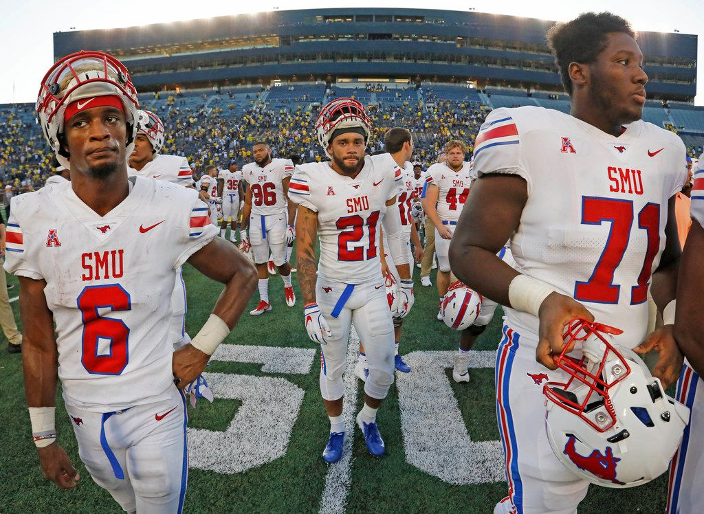 Southern Methodist Mustangs Braeden West (6), Cole Sterns (21), and Southern  Jaylon Thomas (71) walk off the field after the Ponies' loss to Michigan during the SMU Mustangs vs. the Michigan Wolverines NCAA football game at Michigan Stadium in Ann Arbor, Michigan on Saturday, September 15, 2018. (Louis DeLuca/The Dallas Morning News)