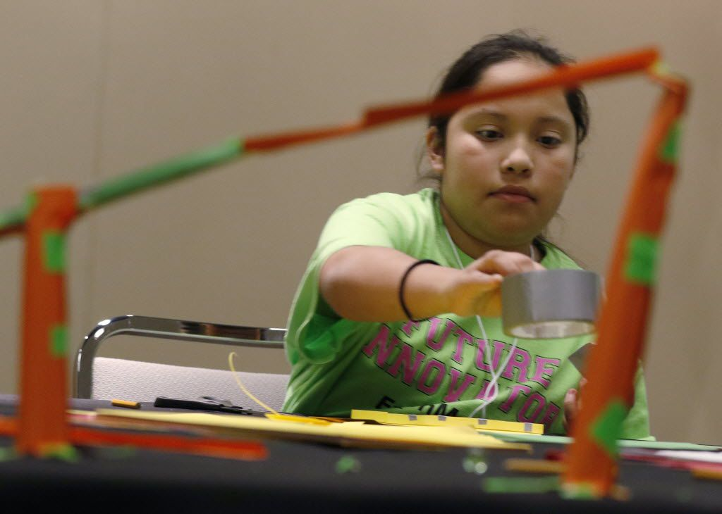 Salma Pacheco helps her teammates construct a roller coaster that will keep a marble rolling as long as possible in an experiment ExxonMobil sponsored, Introduce a Girl to Engineering Day at the Irving Convention Center on Wednesday, February 24, 2016. A diverse group of 6th-8th graders from Dallas, Irving and Richardson ISDs spent the day building marble roller coasters and marshmallow launchers culminating in a friendly competition. (David Woo/The Dallas Morning News)