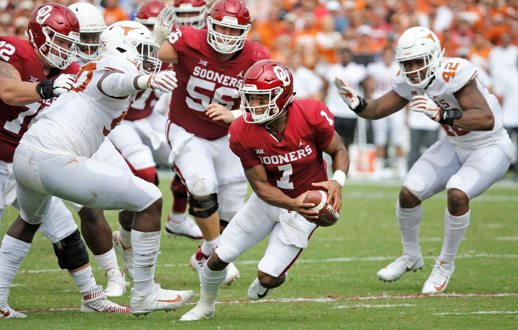 Oklahoma Sooners quarterback Kyler Murray (1) looks for room to run as he is pressured by Texas Longhorns defenders Marqez Bimage (42) and Charles Omenihu (90) in the first half during the University of Texas Longhorns vs. the Oklahoma Sooners NCAA football game at the Cotton Bowl in Dallas on Saturday, October 6, 2018. (Louis DeLuca/The Dallas Morning News)