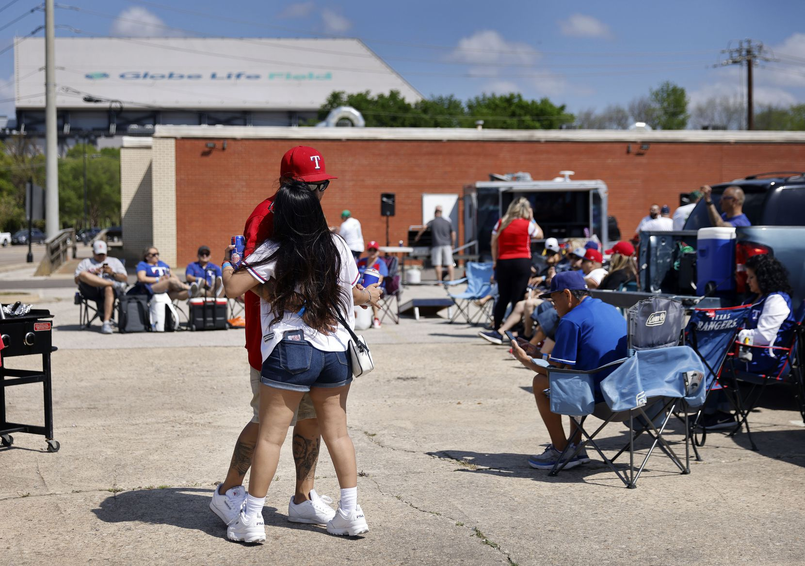 Texas Rangers fans Angela Zurita and her boyfriend Pedro Martinez danced to country music during an Opening Day tailgate party on private property near Globe Life Field in Arlington, Monday, April 5, 2021. The Rangers are facing the Toronto Blue Jays in the home opener. (Tom Fox/The Dallas Morning News)