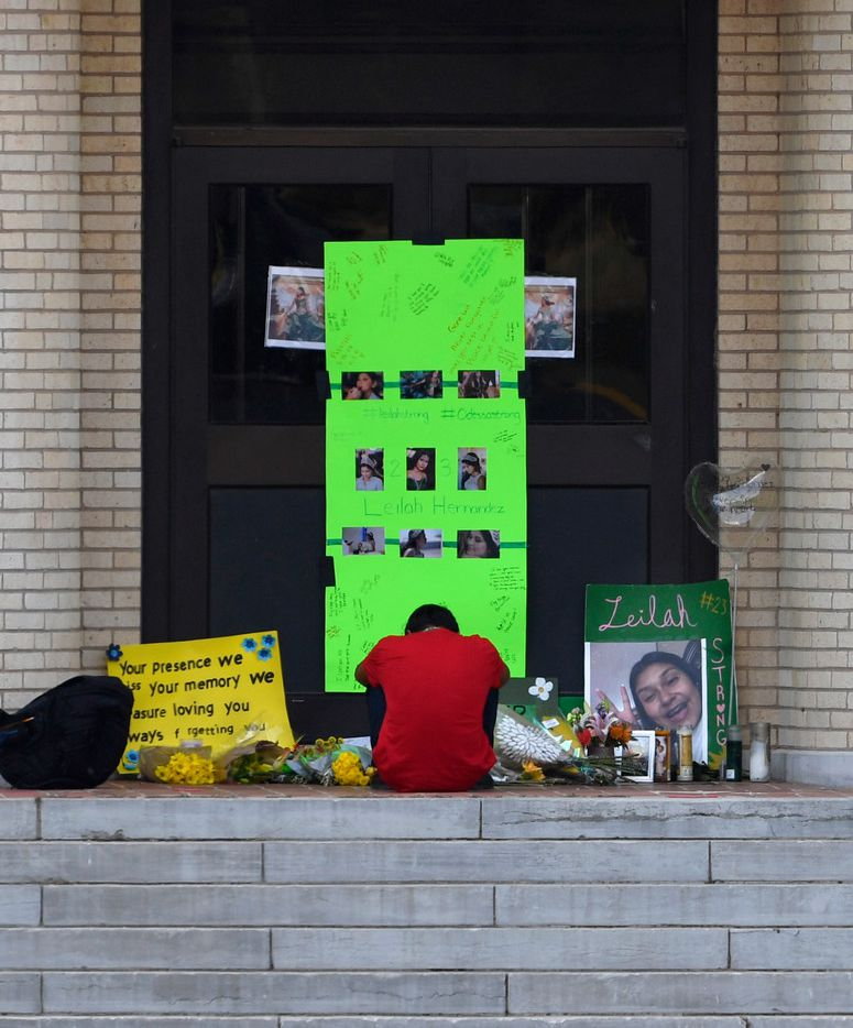 A student sits before the memorial for Leilah Hernandez on the front steps of Odessa High School, Tuesday Sept. 3, 2019. in Odessa, Texas. The 15 year-old student was the youngest of seven people killed in a shooting rampage on Saturday.