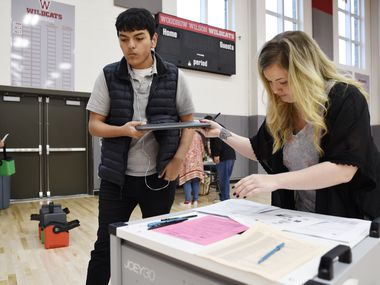 Woodrow Wilson High School sophomore Eric Yañez receives a laptop from special education teacher Cori Wilson, right, to take home for spring break in case Dallas students can't return to school due to COVID-19.
