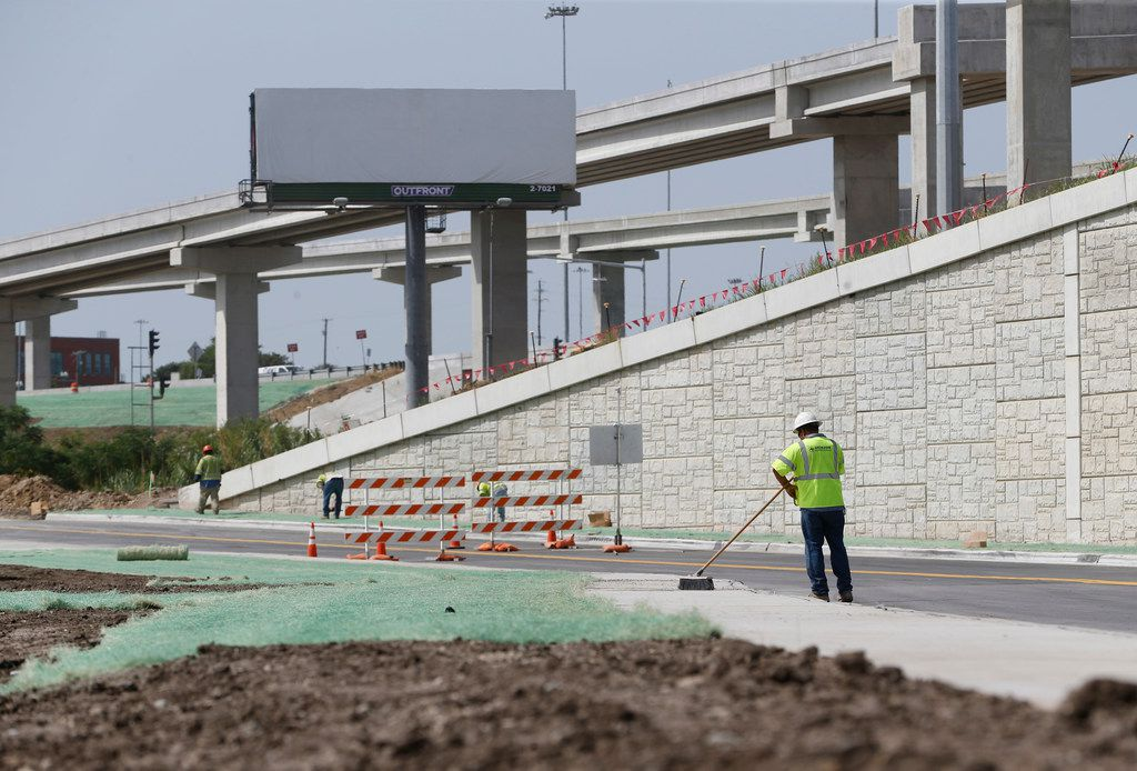A construction worker sweeps the sidewalk at the intersection of Interstate 35W and 4th Street.