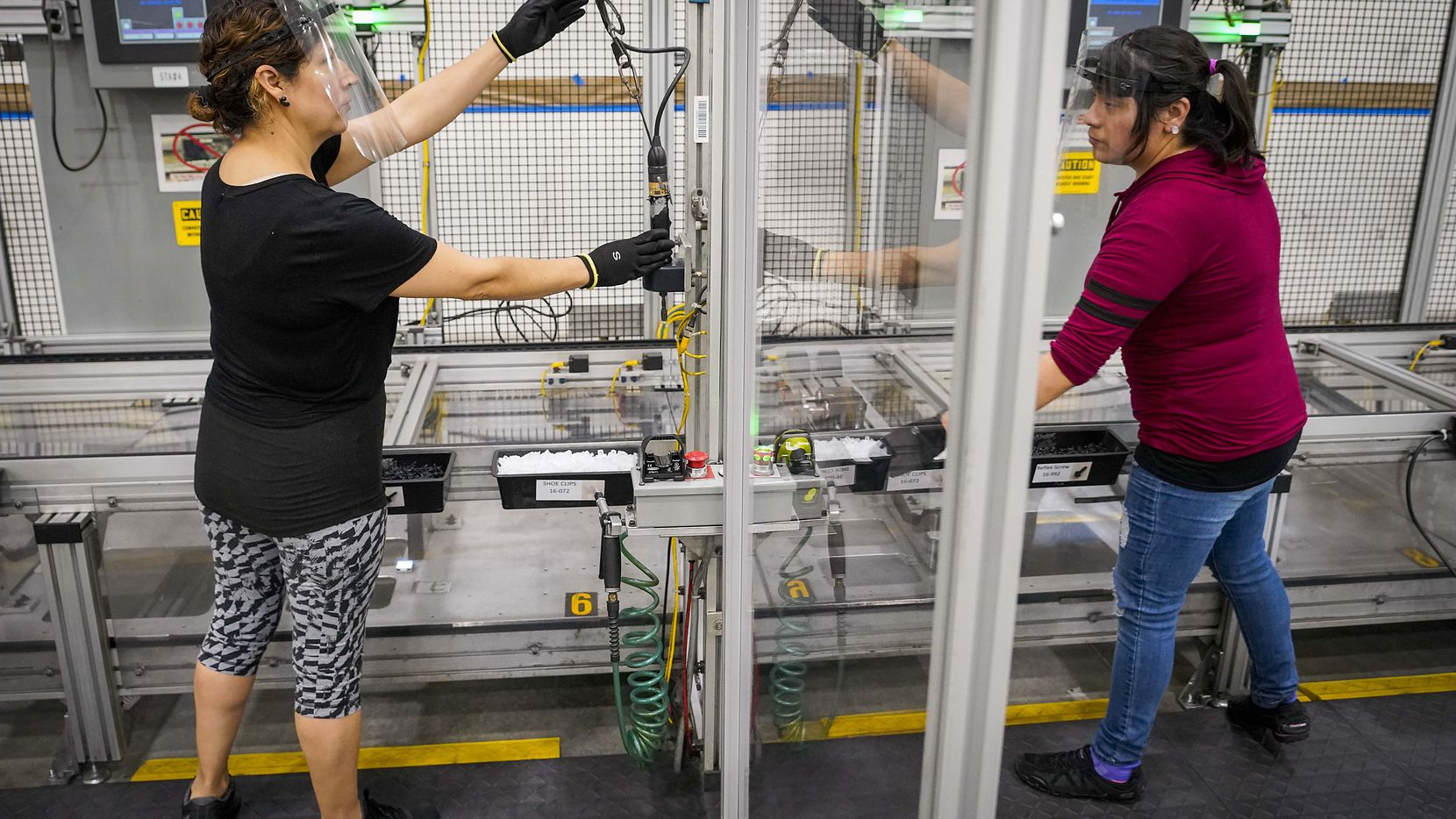 Blanca Ortega, left, and Sacnite Sanchez are separated by a clear barrier on a production line at Flex-N-Gate Texas. The Grand Prairie auto parts supplier built its own barriers as part of an effort to improve worker safety during the pandemic.