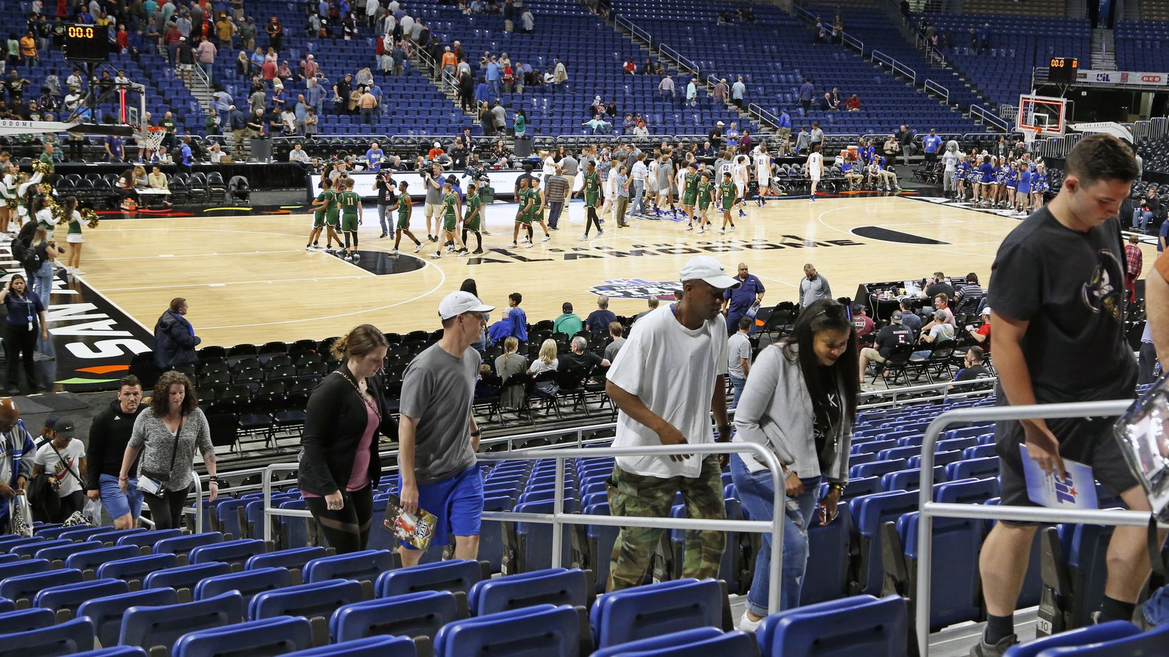 At the conclusion of the final UIL Class 3A state semifinal, fans depart as the rest of thee tournament was suspended on March 12, 2020 at the Alamodome.