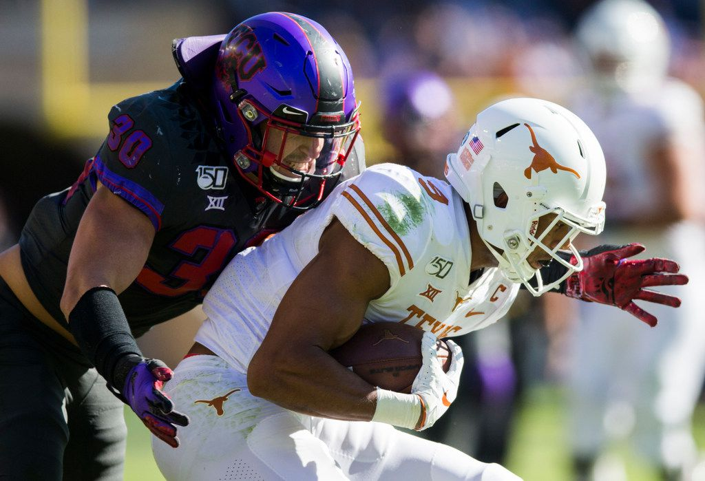 TCU Horned Frogs linebacker Garret Wallow (30) tackles Texas Longhorns wide receiver Collin Johnson (9) during the second quarter of an NCAA football game between the University of Texas and TCU on Saturday, October 26, 2019 at Amon G Carter Stadium in Fort Worth.