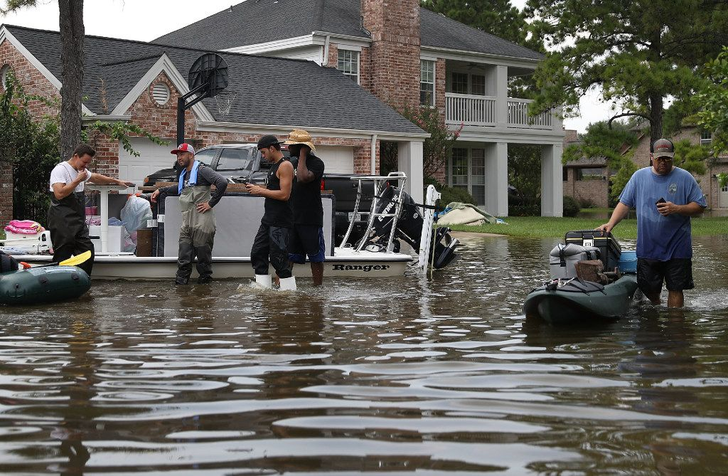 People use boats to help bring items out of homes in the Houston area where torrential rains from Hurricane and Tropical Storm Harvey caused flooding.