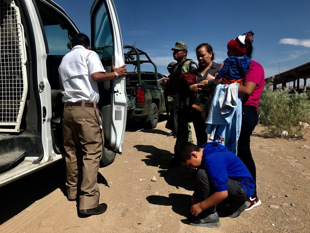 Two Honduran mothers and their children on Friday as they are about to be  transferred from the Mexican national guard to immigration officials who will usher them to a holding facility in Juarez. The boy was asked to remove the laces from his shoes.