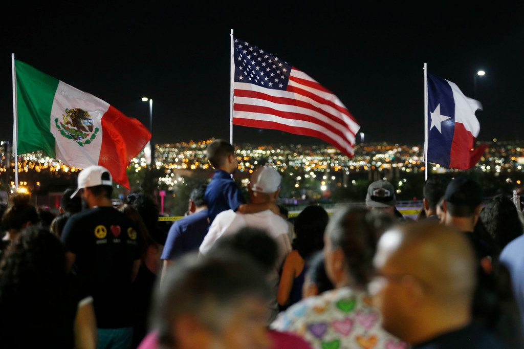 Flags wave in the wind as people gather at the site of a makeshift memorial for victims of the mass shooting at the shopping complex near the Walmart in El Paso on Monday, August 5, 2019.