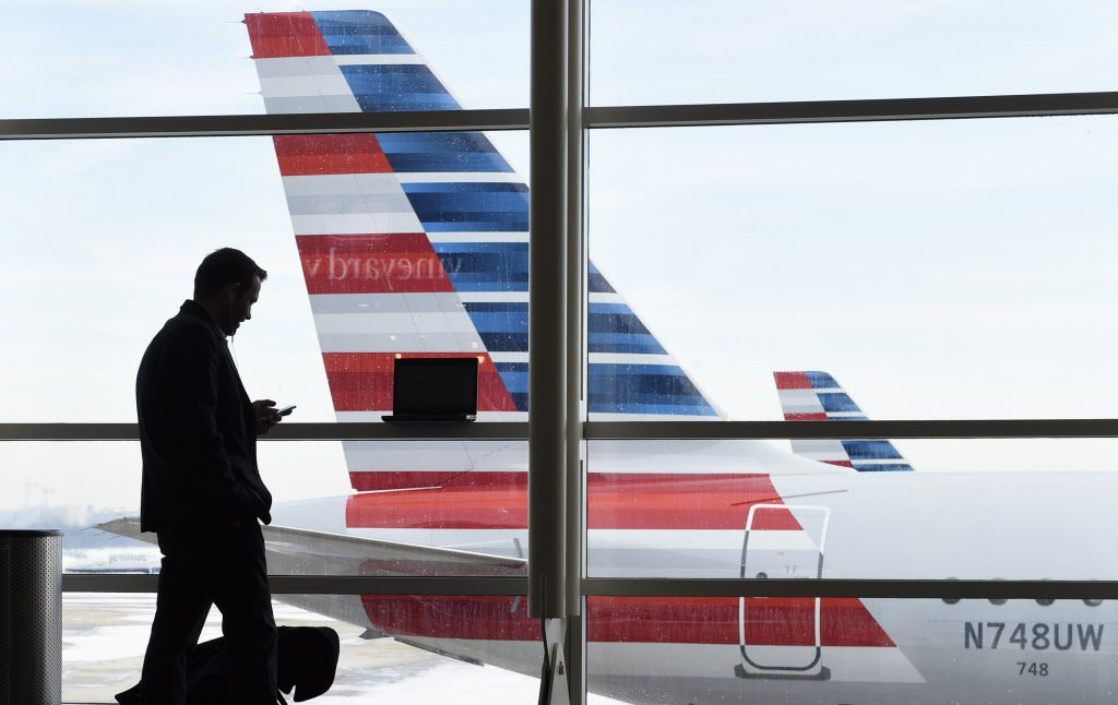 A passenger talks on the phone as American Airlines jets sit parked at their gates at Washington's Ronald Reagan National Airport on Jan. 25, 2016