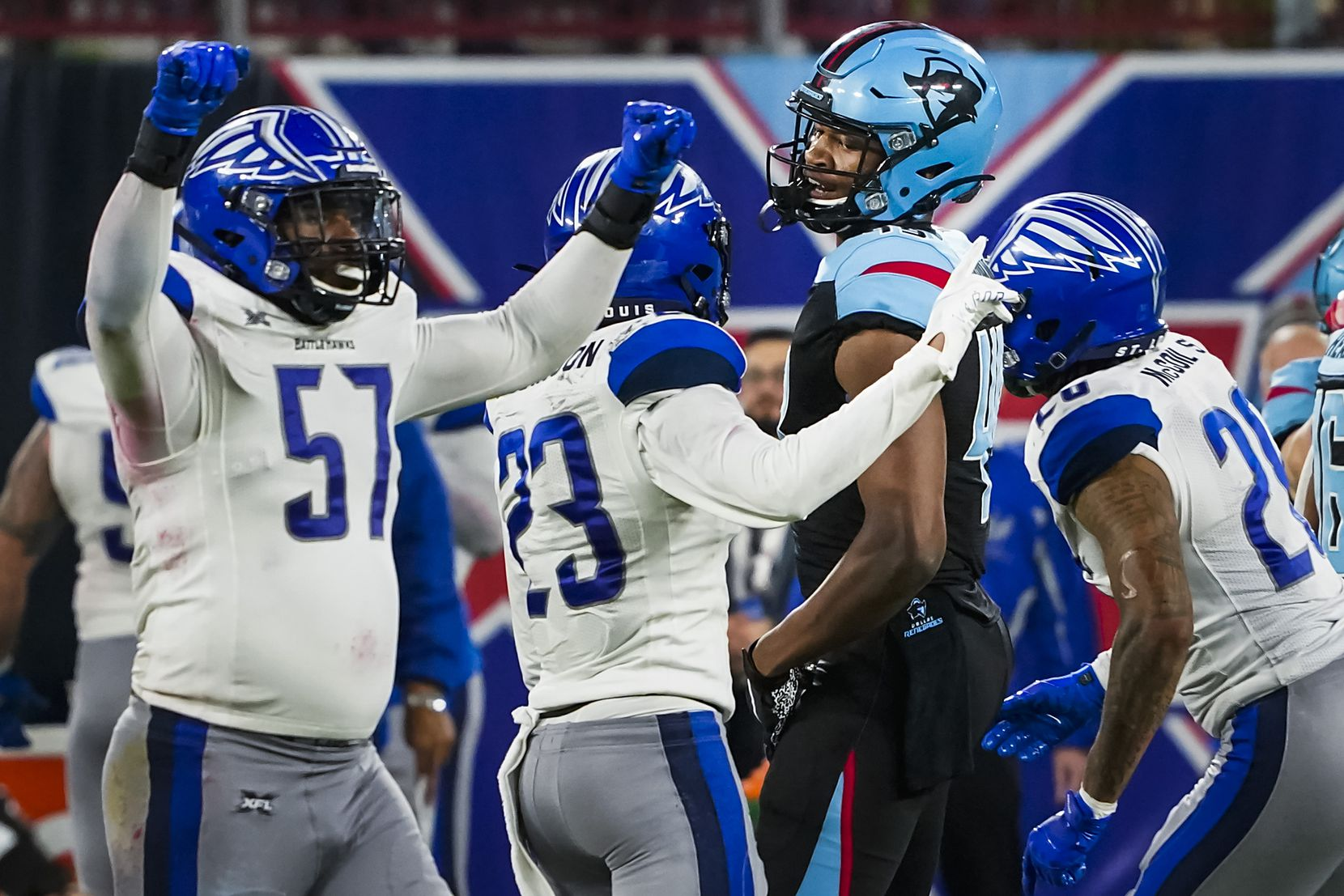 Dallas Renegades tight end Donald Parham (49) looks back as St. Louis Battlehawks linebacker Terence Garvin (57) and safety Kenny Robinson (23) celebrate after an interception in the final minute of an XFL football game at Globe Life Park on Sunday, Feb. 9, 2020, in Arlington.