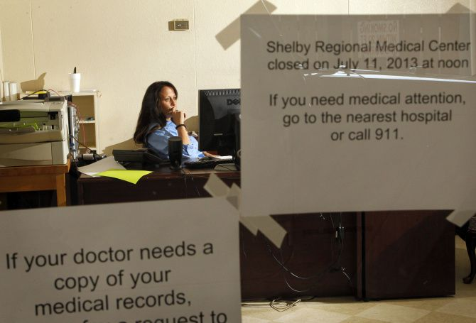 """Though she lost her job when Shelby Regional Medical Center closed, former nurse and quality coordinator Jana Danley still shows up to answer phones and counsel worried patients. A sign near her desk advises people needing care to go to """"the nearest hospital,"""" but it is 21 miles away."""