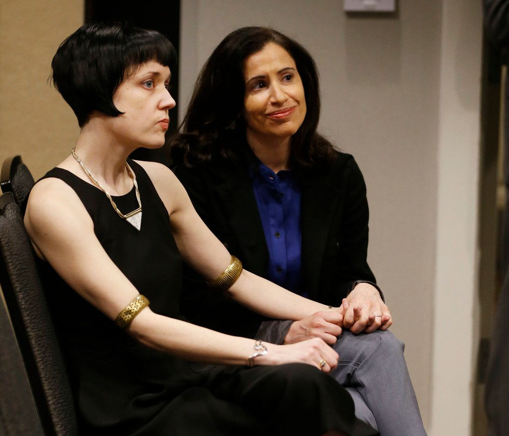 "Bryn Esplin (left) and her spouse, Fatma Marouf, listen during a press conference in Fort Worth. Marouf and Esplin were told they can't foster a refugee child because they don't  ""mirror the Holy Family,"" by a Texas affiliate of the U.S. Conference of Catholic Bishop."