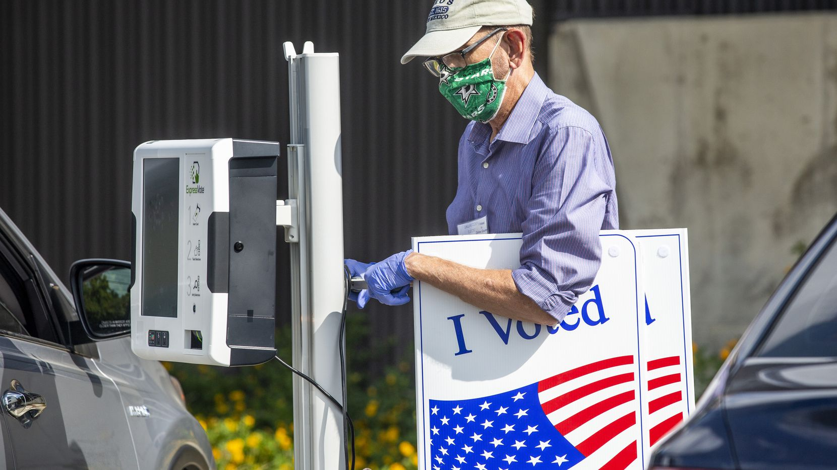 "Election poll worker Daryl Hinshaw wheels a curbside voting machine to a parked voter during the early voting period for the general U.S. election at Fretz Park Public Library in Dallas on Oct. 20, 2020. This is only Hinshaw's second election working as a poll worker, but both this one and the democratic run-off in July he worked took place during the COVID-19 pandemic. ""The mask is mostly the thing that's different, but it doesn't take very long once [voters] are in the door,"" he said. ""But we do curbside voting for people who have mobility issues or are high-risk compromised, or for those who just don't want to come inside."""