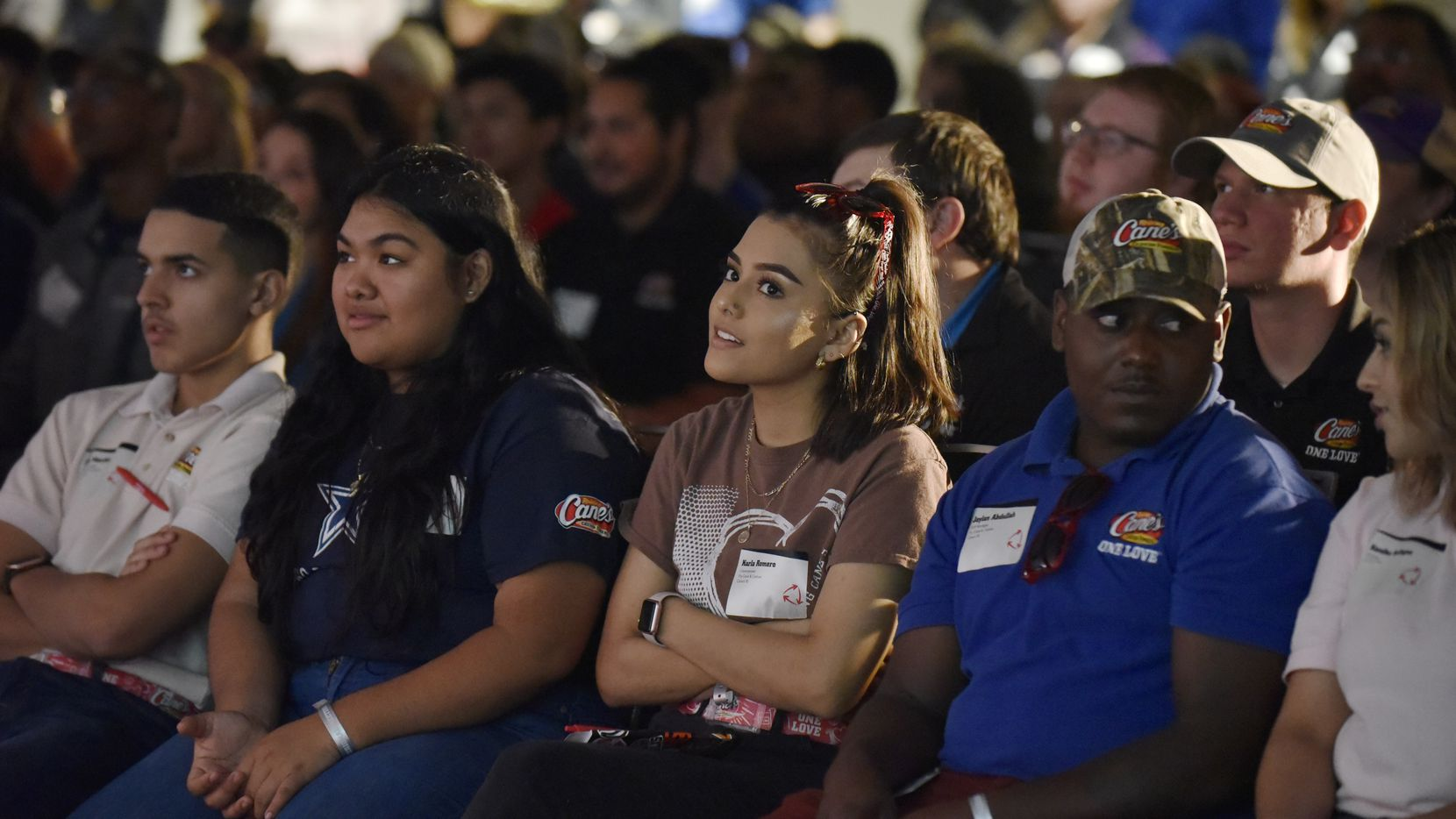 Raising Cane's crewmembers Astrid Mateo, second from lleft, Karla Romero and shift manager Jaylan Abdullah, right, listen to a speaker at a regional meeting in Frisco.