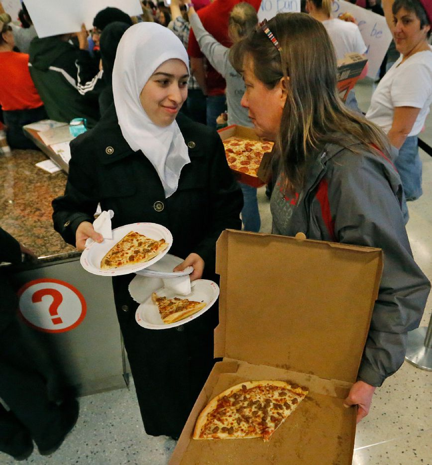 Nour Alnachawazr, left, and Liz Ward, right, work together to distribute pizza to hungry protesters  at the international arrivals gate in Terminal D at DFW Airport on Sunday, January 29, 2017. (Louis DeLuca/The Dallas Morning News)