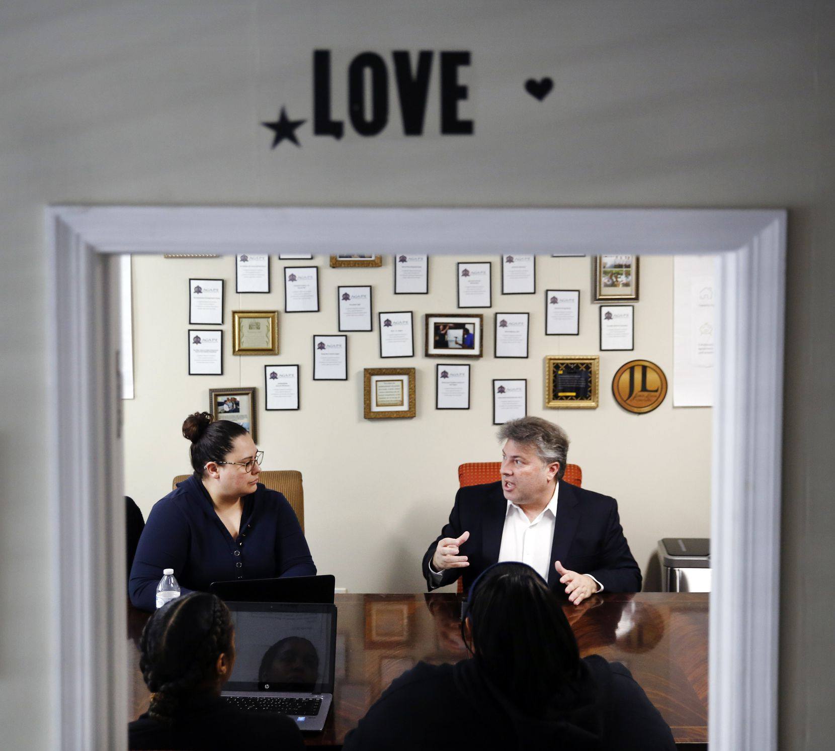 Financial counselor Todd Mark (right) delivers money advice to staffmember Adriana Balderas (facing, left) and others at Agape Resource & Assistance Center in Plano, Texas, Thursday, January 24, 2019.