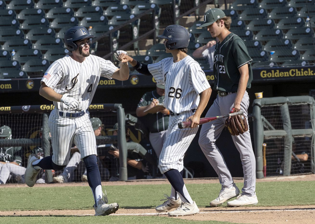 Keller Aidan Connors, (4), left, celebrates with base runner, Colten Vargas, (26), after a sacrifice out as Houston Strake Jesuit pitcher, Carson Brown, (23), looks on during the fourth inning of the 2021 UIL 6A state baseball semifinals held, Friday, June 11, 2021, in Round Rock, Texas.  Keller defeated Strake Jesuit 7-1.  (Rodolfo Gonzalez/Special Contributor)