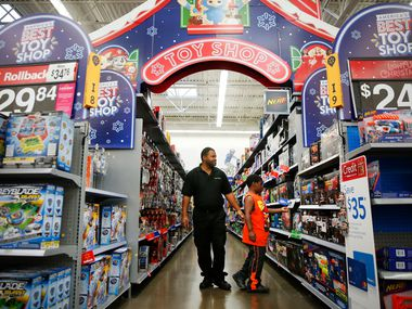 In this 2018 file photo, a father and his son walk down the toy aisle at a Walmart in Dallas.