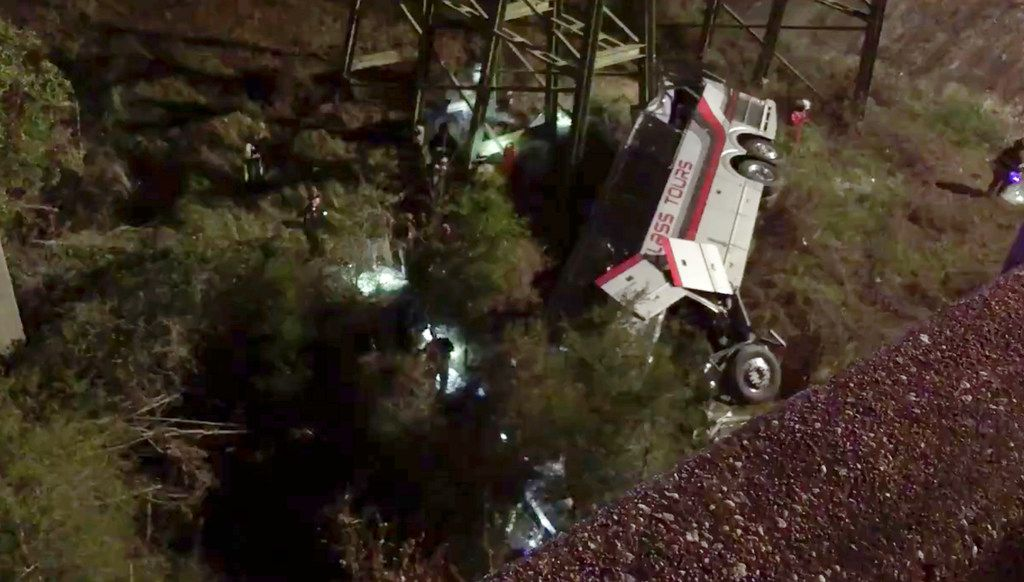 This photo provided by Jesus Tejada shows first responders searching around a bus that plunged into a ravine Tuesday on Interstate 10 near Loxley, Ala.  Several people were on board, and all of them were brought to hospitals in Alabama and Florida, either by helicopter or ambulance.
