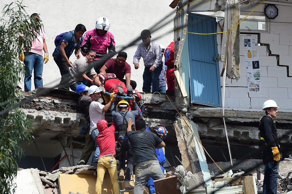 A woman is pulled out of the rubble alive following a quake in Mexico City on Tuesday.