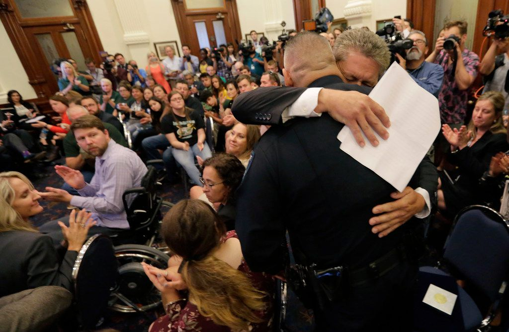 Scot Rice hugs Santa Fe Independent School District police officer John Banda after telling his story during a roundtable discussion in Austin, Texas, Thursday, May 24, 2018, hosted by Texas Gov. Gregg Abbott to address safety and security at Texas schools in the wake of the shooting at Sante Fe, Texas. Rice's wife Flo Rice, a substitute teacher, was carried from the Santa Fe scene of last week's school shooting by officer Banda after she was shot in the leg.