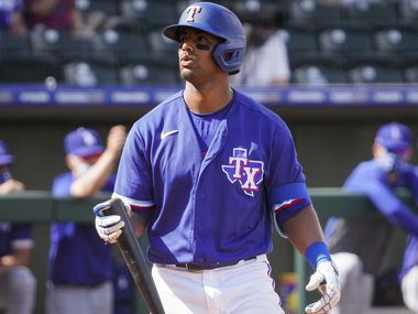 Texas Rangers designated hitter Khris Davis heads back to the dugout after striking out during the sixth inning of a spring training game against the Los Angeles Dodgers at Surprise Stadium on Sunday, March 7, 2021, in Surprise, Ariz.