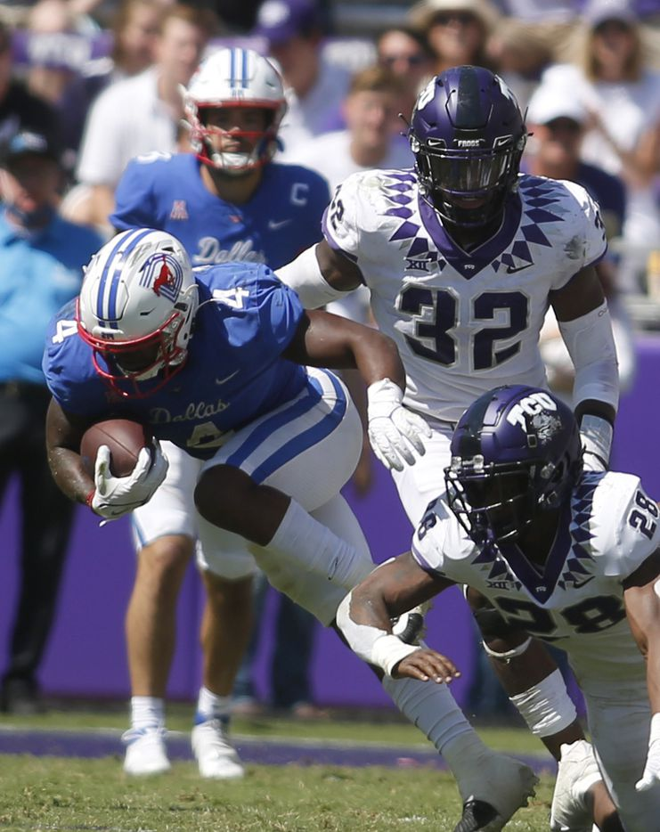 SMU running back Trey Siggers (4) pulls away from TCU defenders Nook Bradford (28) and Ochaun Mathis (32) during a 4th quarter rush. SMU won the game 42-34. The two teams played their NCAA football game at Amon G. Carter Stadium on the campus of TCU in Fort Worth on September 25, 2021. (Steve Hamm/ Special Contributor)