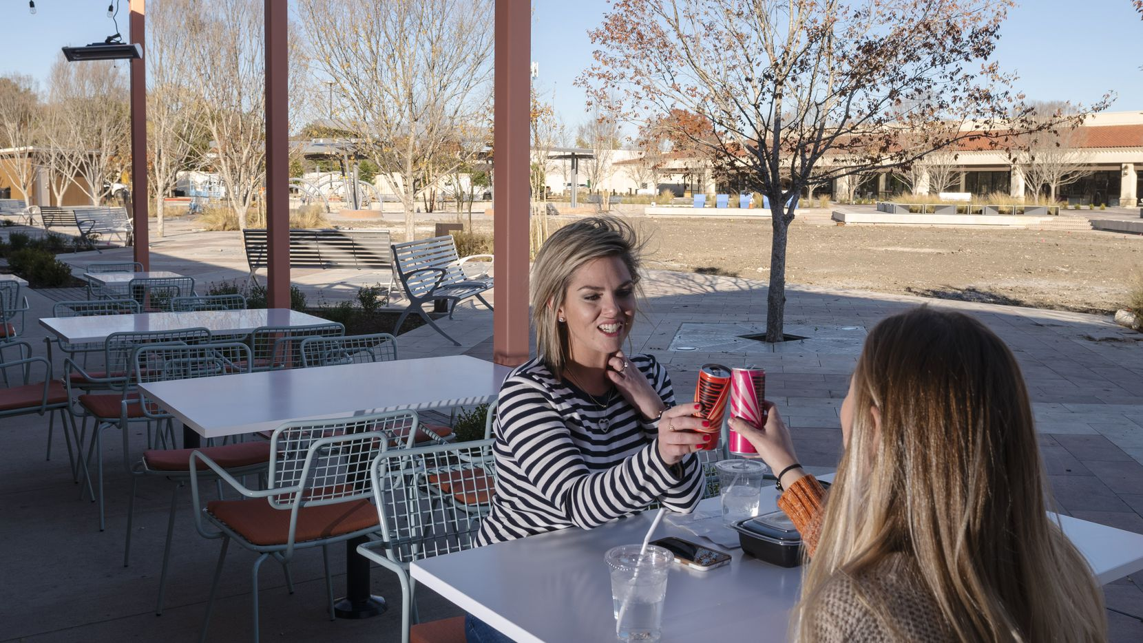 Shelby Presser, left, and Terri Hankins enjoy a pair of beverages after having lunch at Lada, the only open restaurant — so far — facing the park at Hillcrest Village in Far North Dallas. In 2021, the area behind the tree will become a 1.5-acre green space with a half-dozen restaurants with patios.