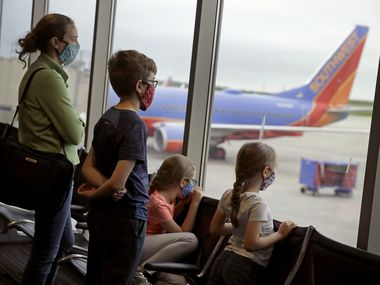 A family wearing masks waits to board a Southwest Airlines flight Sunday, May 24, 2020 at Kansas City International airport in Kansas City, Mo. About three dozen passengers boarded the plane with a capacity of nearly 150 as people are opting not to travel on the normally busy Memorial Day holiday to minimize the chance of spreading COVID-19 coronavirus.