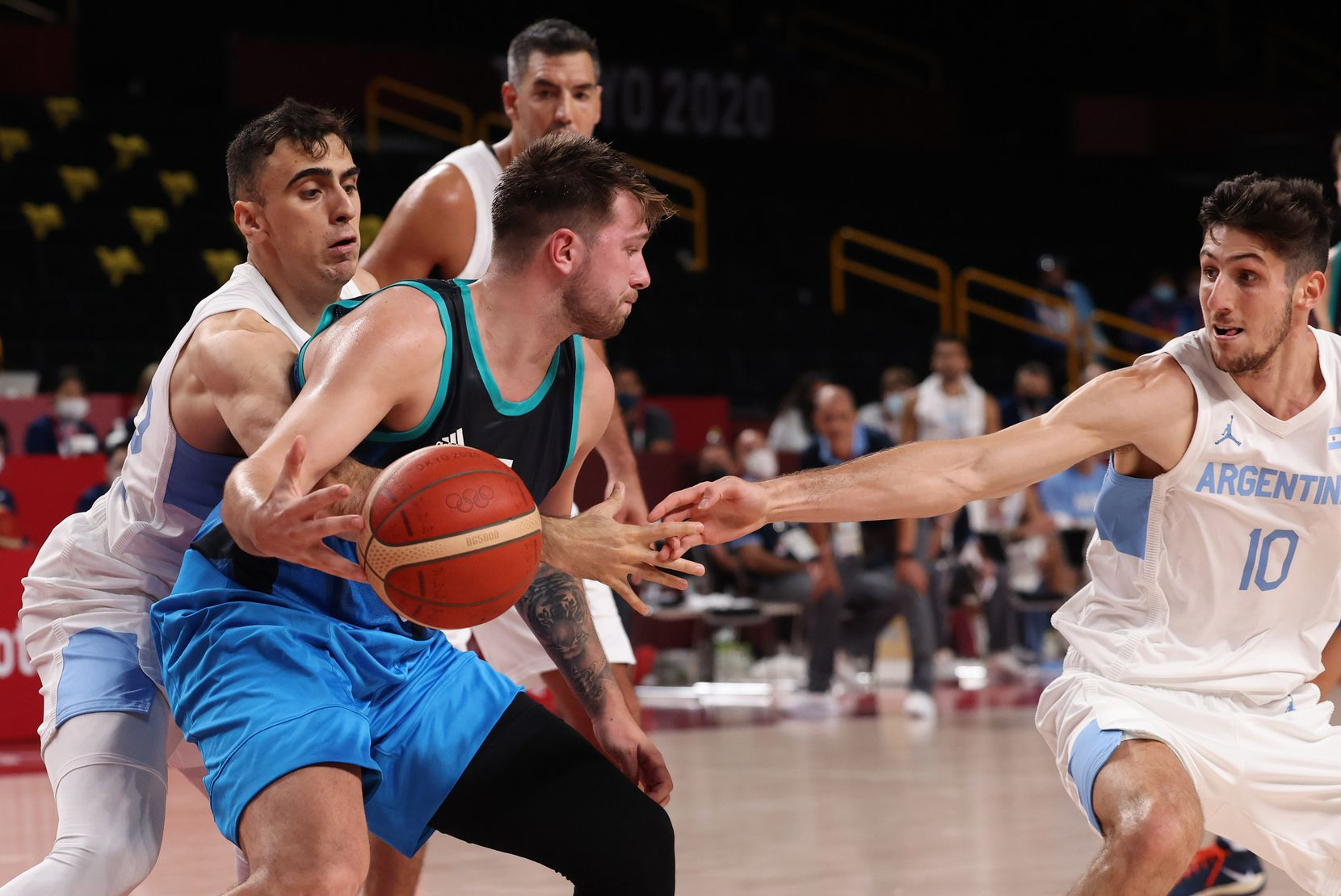 Slovenia's Luka Doncic (77) is defended by Argentina's Juan Pablo Vaulet (22) and Leandro Nicolas Bolmaro (10) in the first half of play during the postponed 2020 Tokyo Olympics at Saitama Super Arena on Monday, July 26, 2021, in Saitama, Japan. Slovenia defeated Argentina 118-100. (Vernon Bryant/The Dallas Morning News)