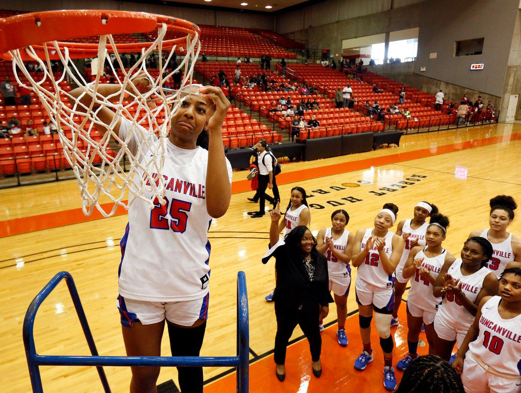 Duncanville's Deja Kelly (25) cuts a piece of the net after she and her teammates defeated Cedar Hill in the Class 6A Region I championship game at Wilkerson-Greines Activity Center in Fort Worth, Saturday, February 29, 2020. Duncanville won the title game, 56-54. (Tom Fox/The Dallas Morning News)